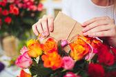 Woman  putting love message in bouquet — ストック写真