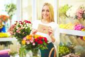 Florist with congratulation message and flowers — Stock Photo