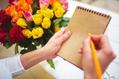 Florist with pencil making notes — Stock Photo