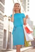Woman with shopping bags calling — Stock Photo
