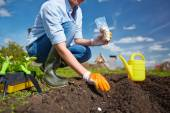 Plantingfarmer sowing seed in garden — Stock Photo