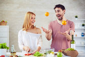 Couple juggling in Kitchen — Stock Photo