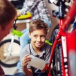Boy lubricating bike wheel chain — Stock Photo #72153035