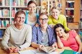 College friends sitting in library — Stock Photo