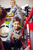 Boy lubricating bike wheel chain — Stock Photo