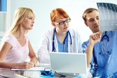 Doctor commenting x-ray to his colleagues — Stock Photo