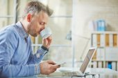 Businessman drinking tea while reading sms — Stock Photo