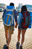 Travelers with backpacks walking in urban environment — Stock Photo