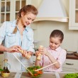 Girl and mother adding salt into vegetable salad — Stock Photo #72161531