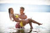 Man holding wife in water — Stock Photo