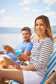 Couple with cocktails sitting on deckchairs — Stock Photo