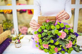 Florist putting envelope in bouquet — Stock Photo