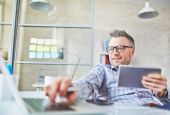 Businessman holding touchpad and typing on laptop — Stock Photo
