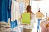 Woman with paperbags standing in boutique — Stock Photo