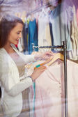Woman choosing blouse in boutique — Stock Photo