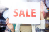 Woman holding paper with sale announcement — Stock Photo