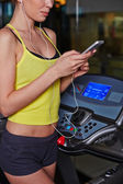 Woman listening to music in gym — Stock Photo