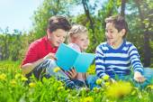 Children with book on lawn — Stock Photo