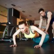 Woman doing push ups on ball with trainer — Stock Photo #76978687