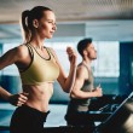 Woman and man running on treadmill — Stock Photo #76979119