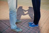 Couple  standing on pavement with their shadows — Stock Photo