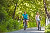 Man and woman riding bicycles in park — Stock Photo