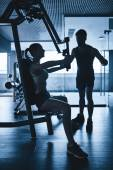 Woman exercising with trainer in gym — Stock Photo