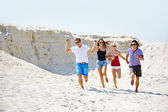 People running down sandy beach — Stock Photo
