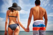 Restful couple in swimwear by the sea — Stock Photo
