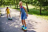 Little girls skateboarding in park — Stock Photo