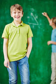 Schoolboy with classmate by blackboard — Stock Photo