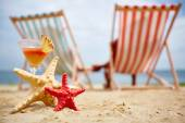 Sea stars with tropical cocktail on beach — Stock Photo