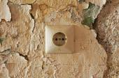 Old electrical outlet on decrepit wall — Stock Photo