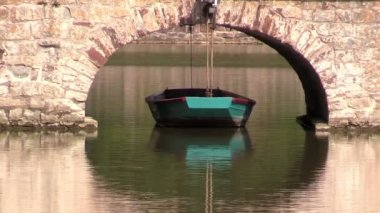 Tied boat near the bridge on pond — Vídeo stock