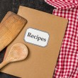 Recipe book with wooden spoons on a red checkered tablecloth — Stock Photo #52784117