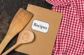 Recipe book with wooden spoons on a red checkered tablecloth — Stock Photo