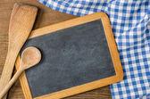 Tableau noir avec des cuillères en bois sur une nappe à carreaux bleu — Photo