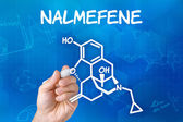 Hand with pen drawing the chemical formula of Nalmefene — ストック写真