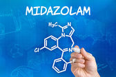 Hand with pen drawing the chemical formula of Midazolam — ストック写真