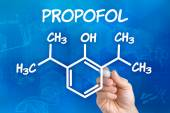 Hand with pen drawing the chemical formula of Propofol — Stock Photo