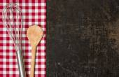 Old baking tray with red checkered table cloth and baking utensils — Stock Photo
