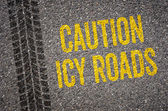 Lane with the text Caution icy roads — Stock Photo