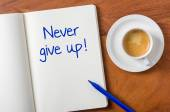 Notebook on a desk - Never give up — Stock Photo