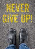 Text on the floor - Never give up — Stock Photo