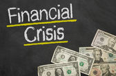Text on blackboard with money - Financial Crisis — Stock Photo