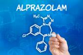 Hand with pen drawing the chemical formula of Alprazolam — Stock Photo