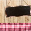 Empty metal sign on a wooden wall with a red checkered decor — Stock Photo #79929404