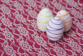 White Easter eggs against a red and white lacy — ストック写真