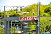 Exit only sign on security door with barbed wire — Stock Photo