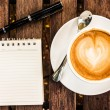 Open a blank white notebook, pen and cup of coffee on wood desk — Stockfoto #54127631
